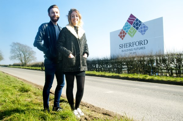 Designers in front of Sherford sign